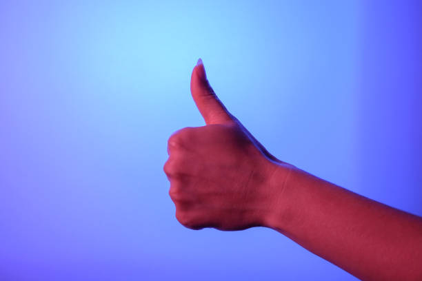 Woman's hand show thumbs up sign on the blue background Woman's hand show thumbs up sign on the blue background approbation stock pictures, royalty-free photos & images