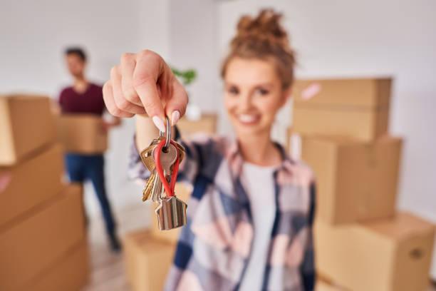 Frau Hand zeigt Schlüssel aus neuer Wohnung – Foto