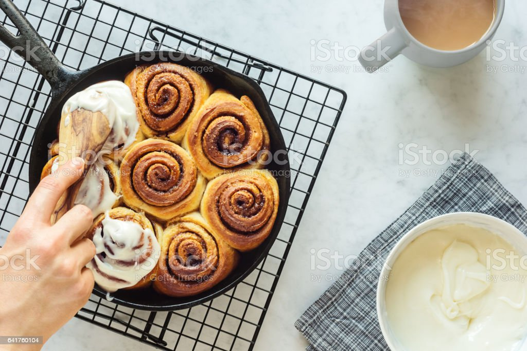 Woman's Hand Spreading Frosting Across Cinnamon Rolls in Skillet stock photo