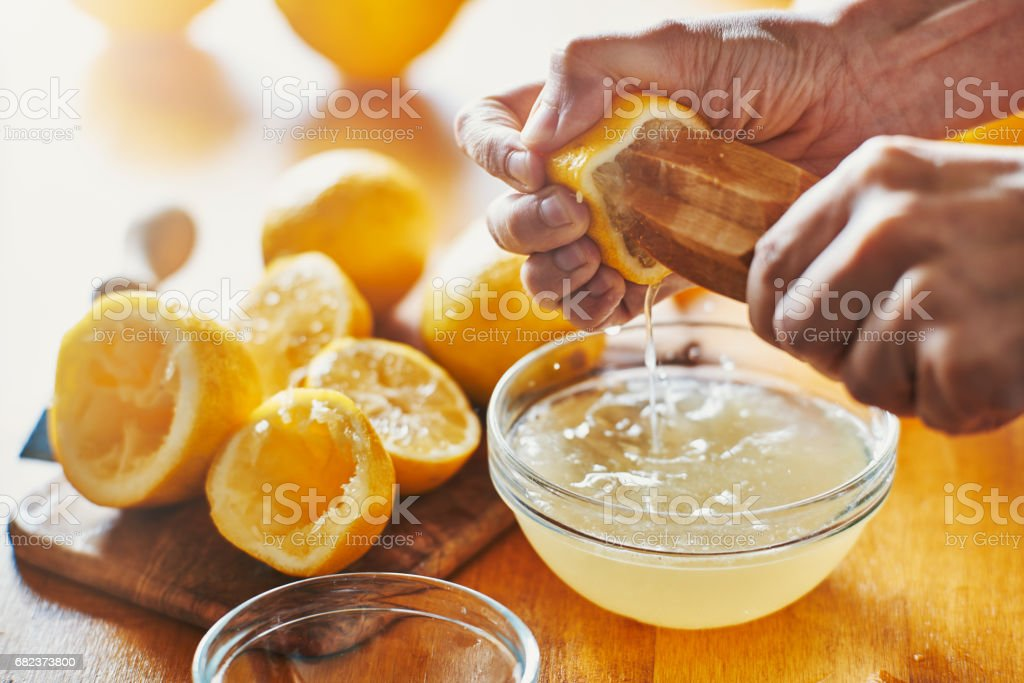 woman's hand squeezing juice from a lemon with wooden tool stock photo