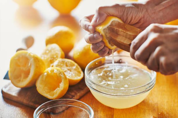 나무 도구와 레몬에서 주스를 짜 내는 여자의 손 - 짠 뉴스 사진 이미지