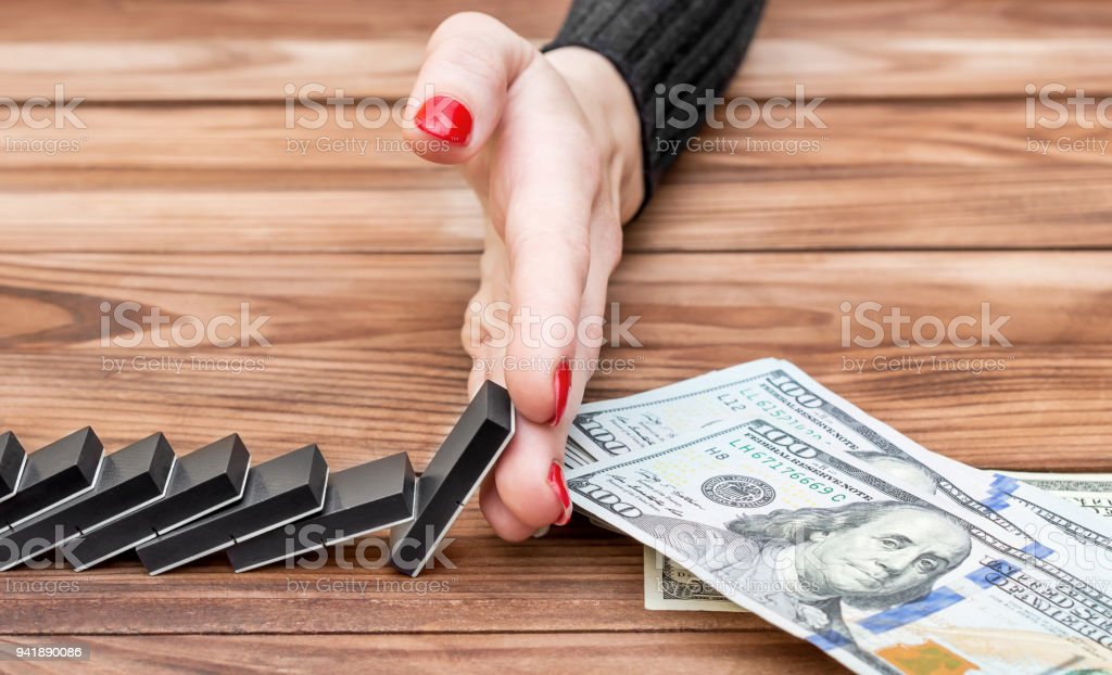 Woman's hand stops domino effect before money. Business concept. stock photo