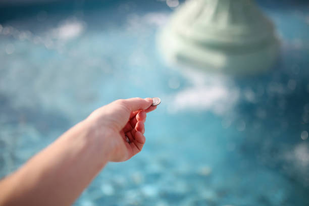 Woman's Hand Throwing Coin in Wishing Fountain stock photo