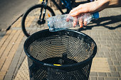 Woman's hand throws empty plastic water bottle into city street trash can on sunny day, close-up