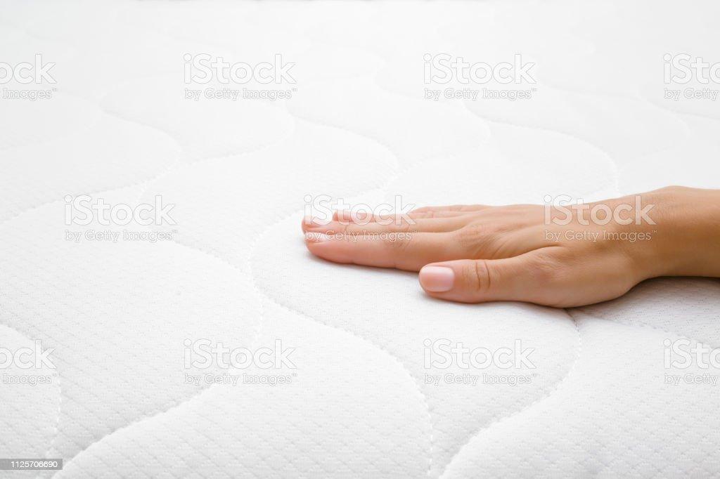 Woman\'s hand touching cloth white mattress. Checking softness. Choice...