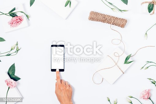 Woman's hand touching smart phone screen among feminine festive flat lay frame with pink flowers, gift boxes, leaves, stems and twine coil. Top view stylish  decoration with empty device display.