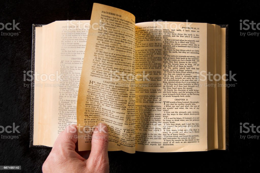 Woman's Hand Turnign Pages In The Bible stock photo