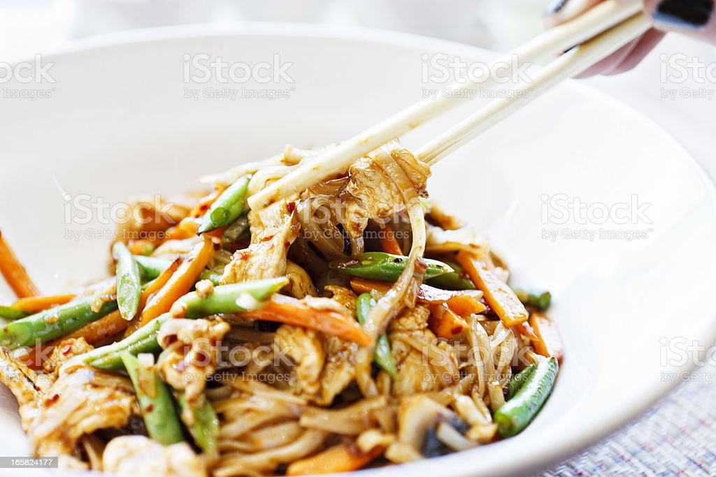 Woman's hand uses chopsticks to serve Thai chicken noodle dish royalty-free stock photo