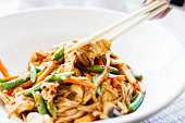 A woman's hand uses chopsticks to lift a portion of  a Thai dish of chicken, stir fried with green beans, julienne carrots. chilli bits and noodles, from a white china bowl.