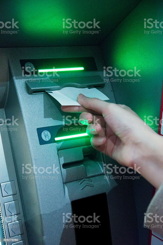 Woman's hand using  ATM on the street at night stock photo