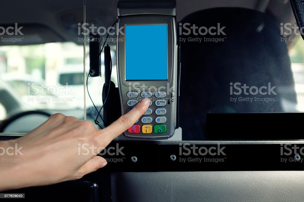 Woman's Hand Using Credit Card Machine on Taxi Cab stock photo
