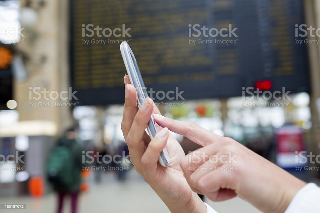 Woman's hand using her cell phone in train station stock photo