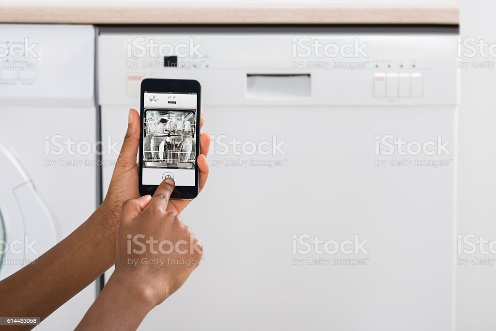 Woman's Hand Using Mobile Phone For Operating Dishwasher stock photo