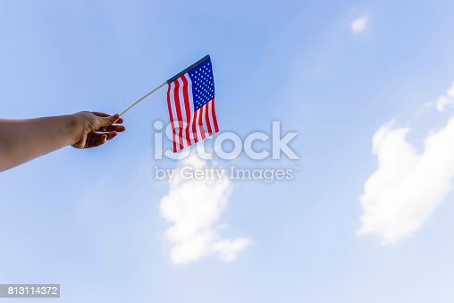 514069232 istock photo Woman's hand waving american flag outside on fourth of July 813114372