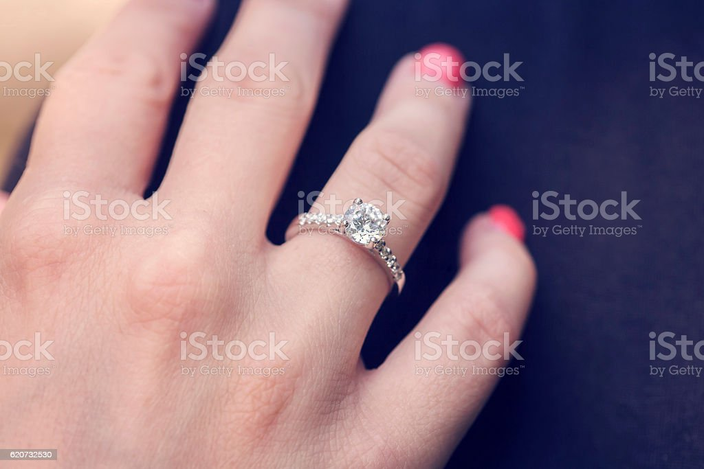 Woman's hand wearing an engagement ring stock photo