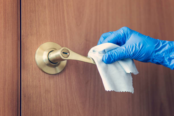 A woman's hand wipes the door handle with wet rag. The maid is washing the doorknob. Prevention of coronavirus and bacterial infections stock photo