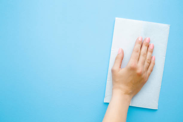 woman's hand wiping pastel blue desk with white paper napkin. general or regular cleanup. close up. empty place for text or logo. top view. - rag stock pictures, royalty-free photos & images