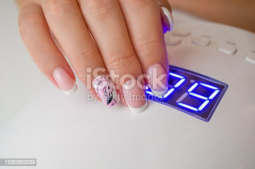 istock A woman's hand with a beautiful summer manicure on the background of a lamp. The nails are covered with a gel polish with a pattern. French manicure. 1330350039