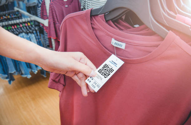 Woman's hand with a cloth hang tags label with QR code in a clothing shop. stock photo