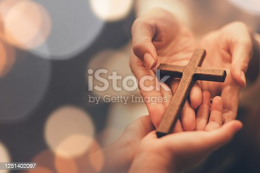 istock Woman's hand with cross .Concept of hope, faith, christianity, religion, church online. 1251402097