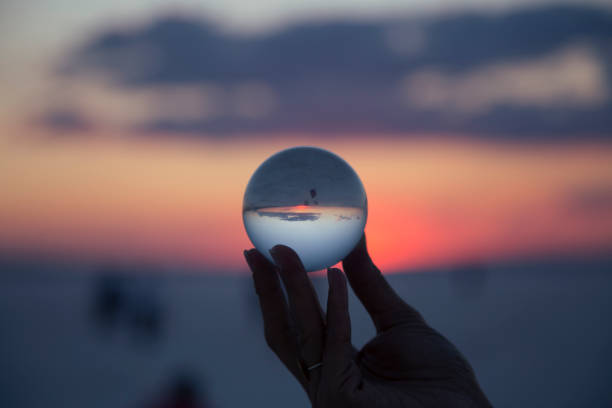 woman's hand with crystal ball Sunset stock photo