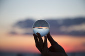 woman's hand with crystal ball Sunset