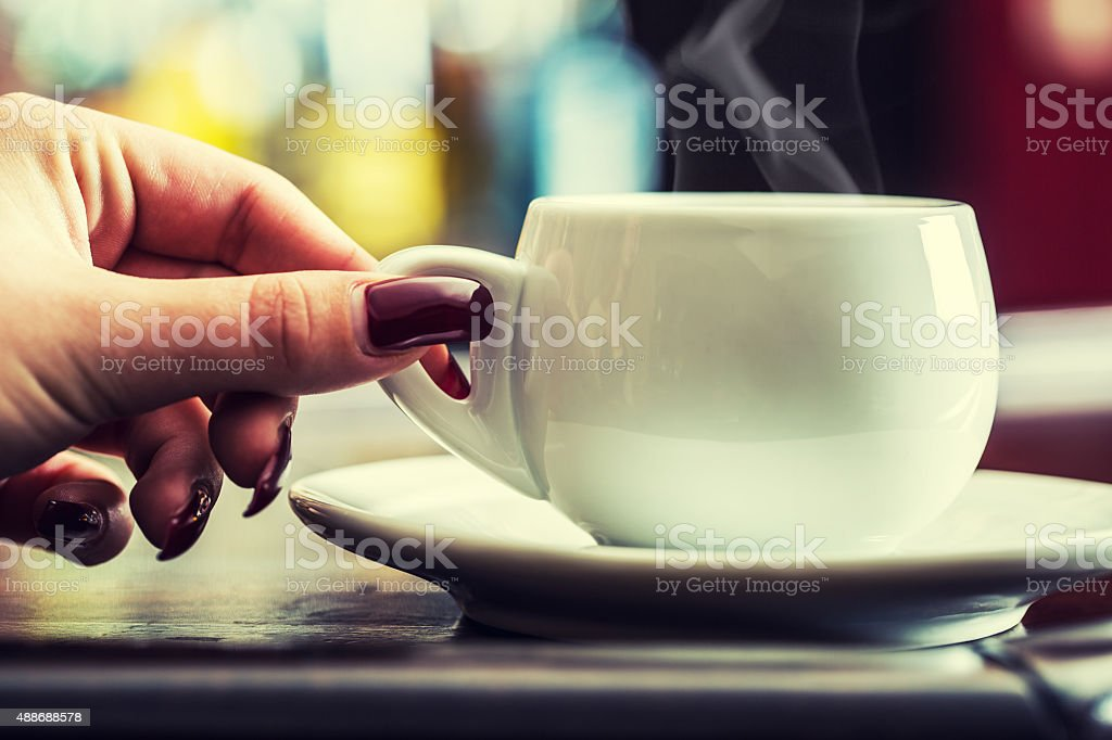 Womans hand with manicured nails holding a cup of coffee stock photo