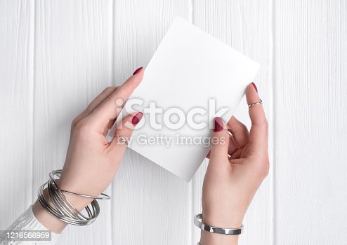 831932306 istock photo Womans hand with minimal pink spring summer manicure design holding greeting card. 1216566959