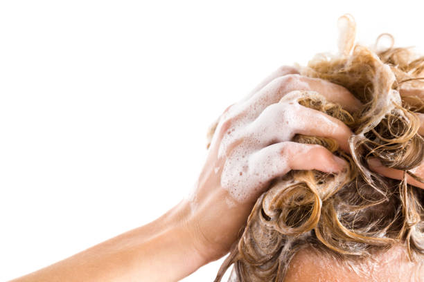 Woman's hand with shampoo washing hair isolated on the white background. Cares about a healthy and clean hair. Beauty salon. Empty place for a text. Woman's hand with shampoo washing hair isolated on the white background. Cares about a healthy and clean hair. Beauty salon. Empty place for a text. dandruff stock pictures, royalty-free photos & images