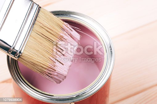 istock Woman's hand with white brush applying pink paint on wooden furniture. 1079938904
