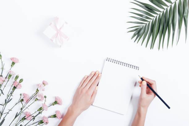 woman's hand writing in a notebook at the desk, top view - folha de caderno imagens e fotografias de stock