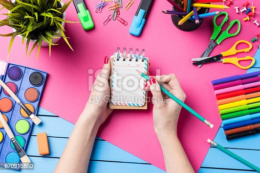 818512928istockphoto Woman's hand writing in empty notebook. School or art background 670915860