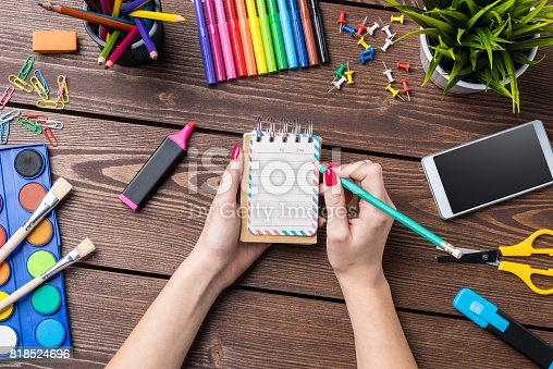818533812 istock photo Woman's hand writing in empty notebook. School or art background 818524696