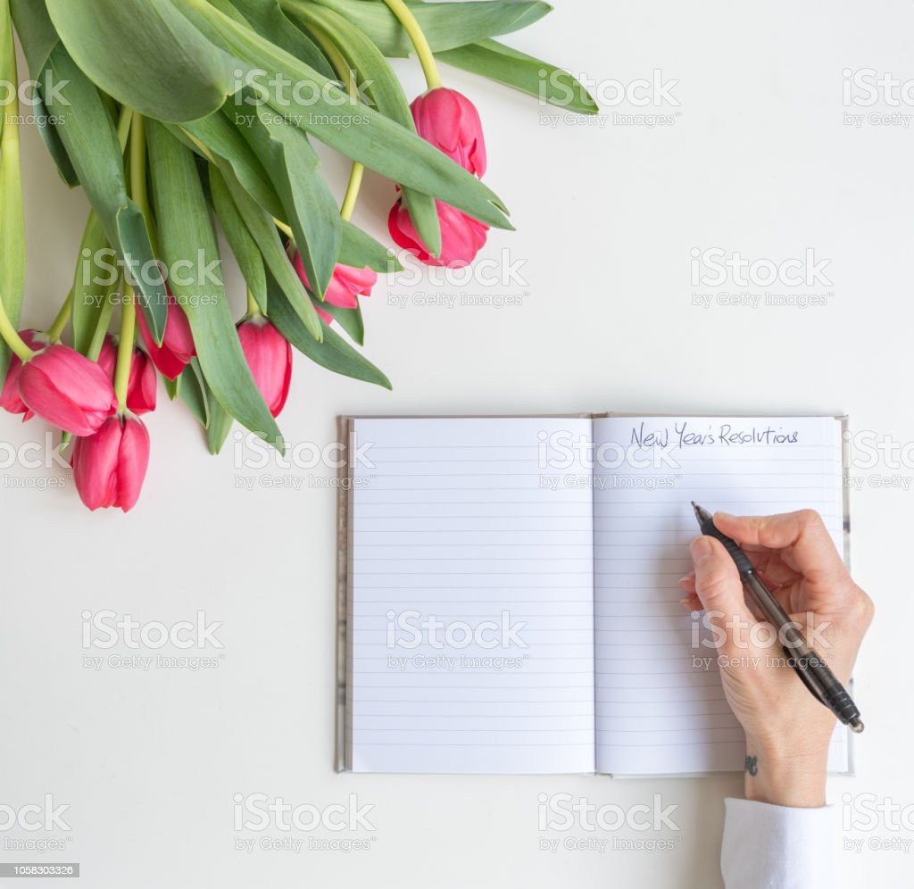 High angle view of red tulips with woman\'s hands holding pen over...