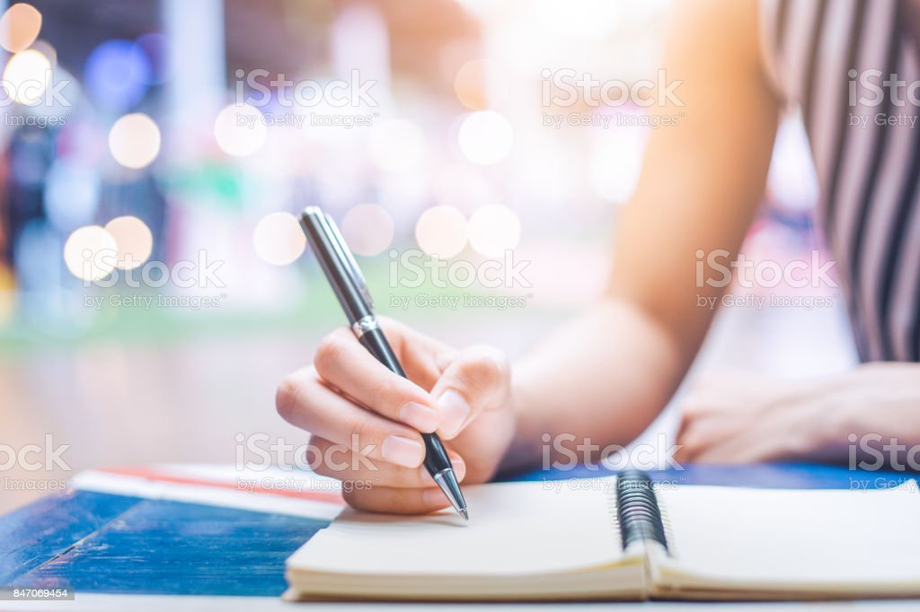 Woman's hand writing on a notebook with a pen on a wooden desk. stock photo