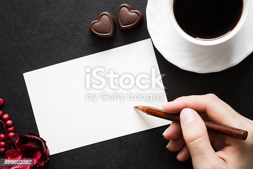 istock Woman's hand writing on the white blank greeting card. Cup of black coffee with chocolate hearts on the dark table. Congratulation concept. Empty place for text of good mood. 889603382