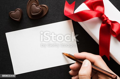 istock Woman's hand writing on the white blank greeting card. Gift box with red ribbon and chocolate hearts on the dark table. Congratulation concept. Empty place for text of good mood. 889600440