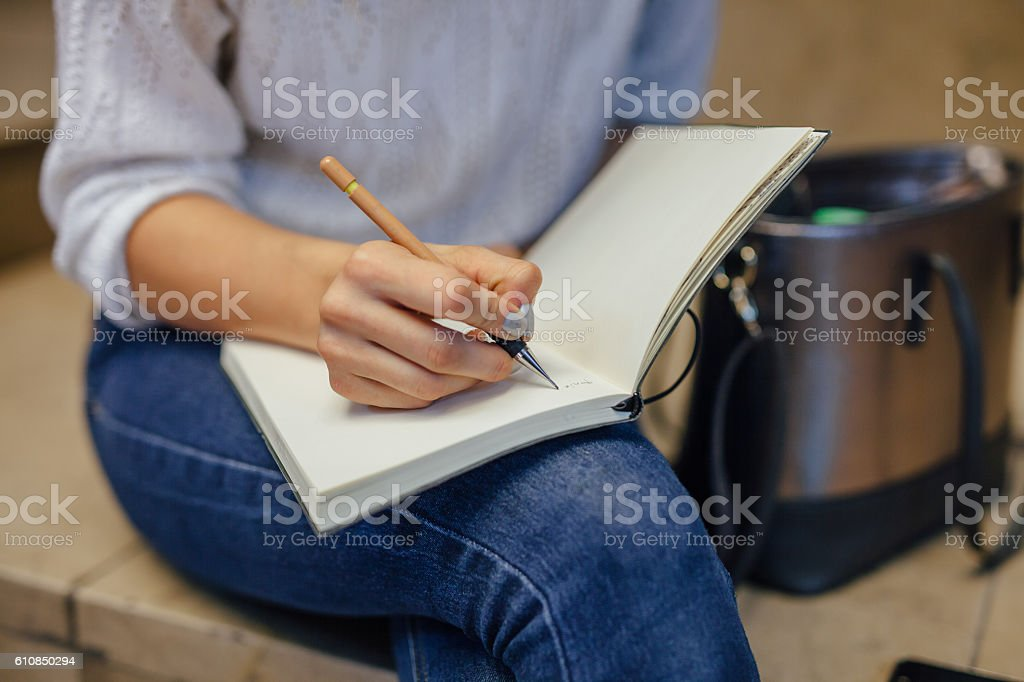Woman's hand writing something at the notebook. Indoor stock photo