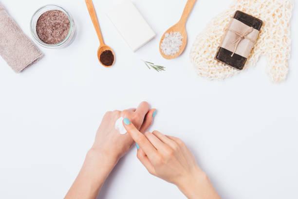 frau hände verwenden kosmetische creme neben badeaccessoires - makeup selbst gemacht stock-fotos und bilder