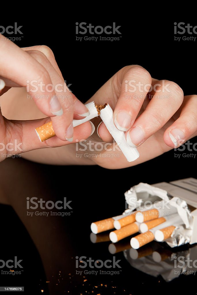 Woman's hands breaking a cigarette in half with a carton royalty-free stock photo