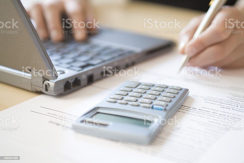 Woman's Hands Calculating Home Finances At Desk stock photo