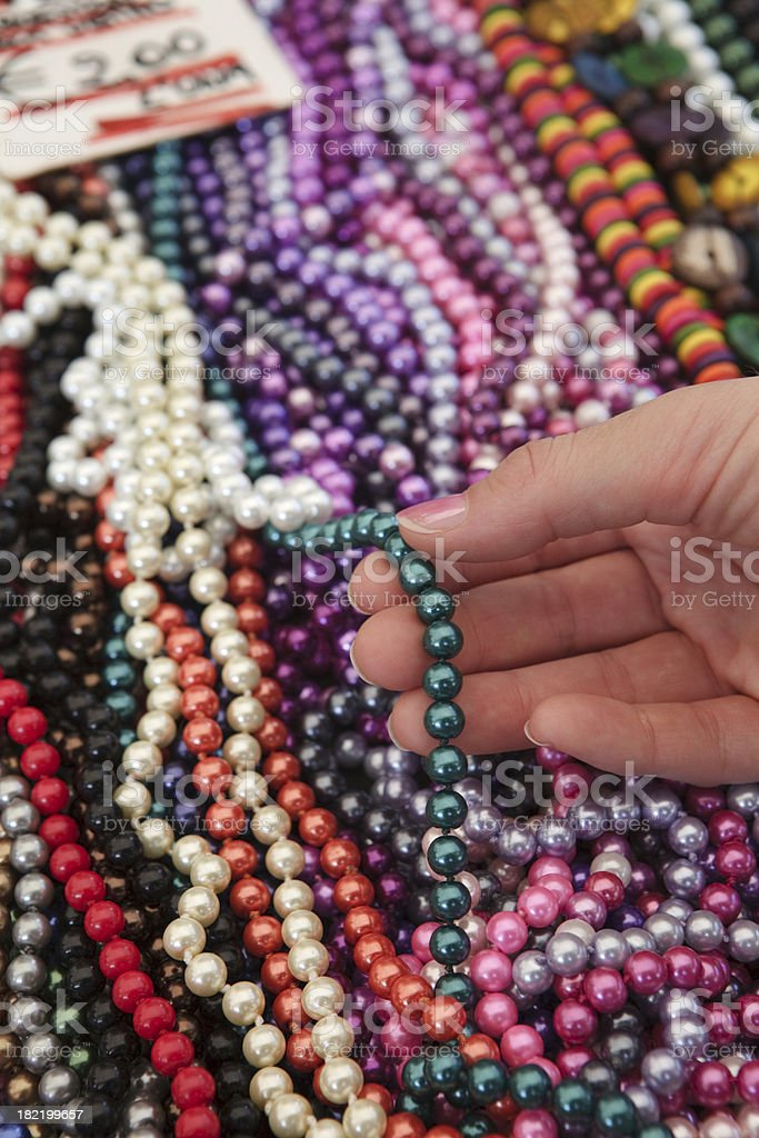 Woman's hands choosing a fake pearl necklace at street market royalty-free stock photo