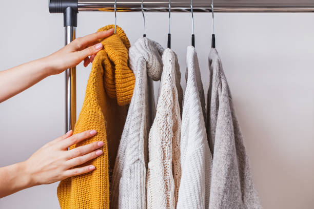 Woman's hands choosing yellow knitted sweater among others on hanger stock photo