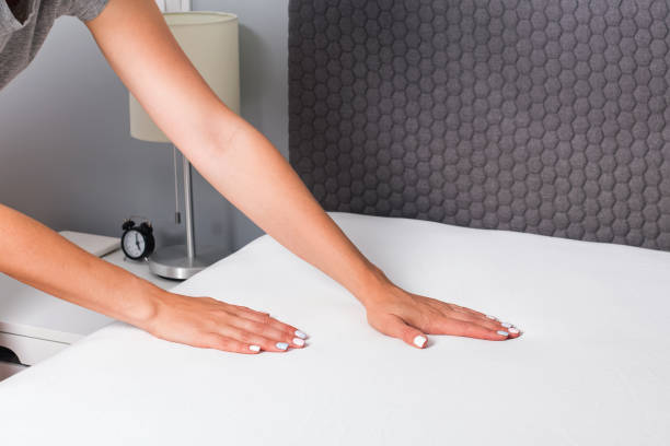 Woman's hands close-up making the bed. stock photo
