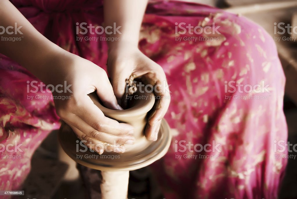 Woman's hands creating pottery on wheel royalty-free stock photo
