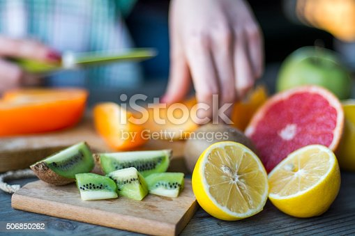 istock Woman's hands cuts fresh persimmons 506850262