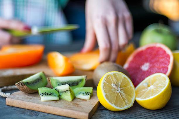 woman's hands cuts fresh persimmons - 柑橘類水果 個照片及圖片檔