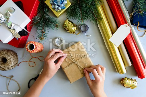 istock Woman's hands decorate present box on gray wooden background. New Year and Christmas decorations concept. 1043568904