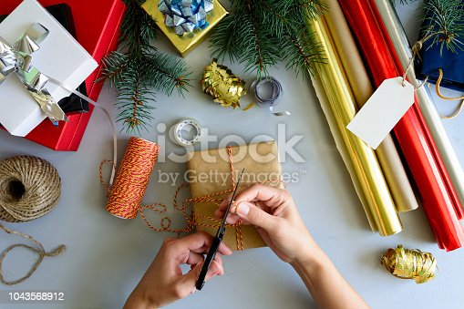 istock Woman's hands decorate present box on gray wooden background. New Year and Christmas decorations concept. 1043568912
