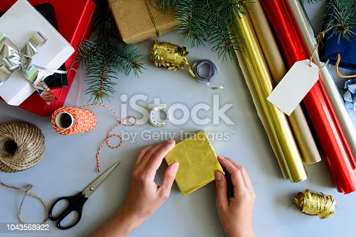 istock Woman's hands decorate present box on gray wooden background. New Year and Christmas decorations concept. 1043568922
